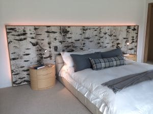 Photo of a headboard made from Bark House birch bark material - innovative and sustainable wood products on elemental green
