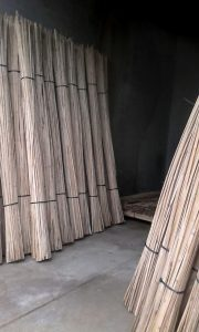 Photo of many bound bamboo bunches resting against two walls - bamboo engineered materials on elemental green