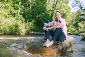Brandon Bryant Headshot, Red Tree Builders, man sitting on a rock in a river